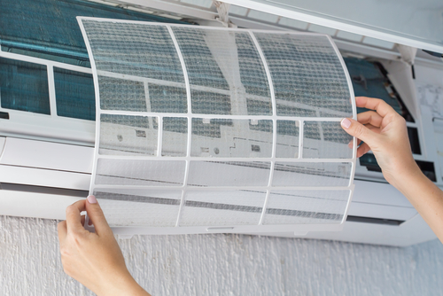 technicial putting back air conditioner filter after cleaning