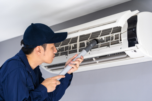 ac technician vacuuming air conditioner filters