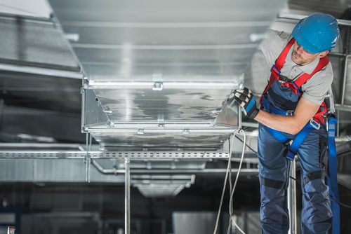 technician implementing a ventilation system in an industrial space