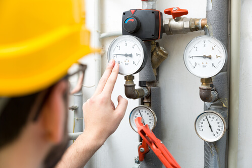 technician checking pressure meters for industrial heating system
