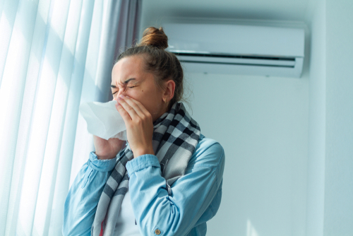 woman ill and sneezing due to dirty air conditioning filters