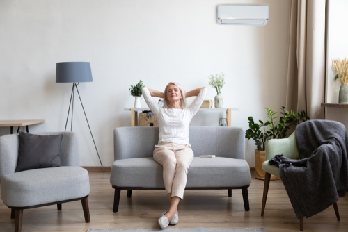 Woman Relaxing In Front Of A Split Air Conditioner in the living room