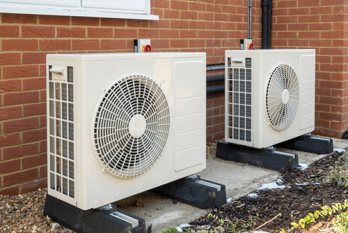Two Air Source Heat Pumps Installed On The Exterior Of a House